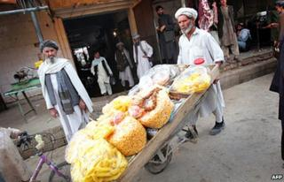 An Afghan vendor pushes his snack cart in a market in Lashkar Gah in March 2010