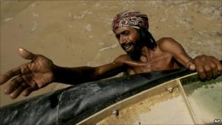 Pakistani flood survivor hangs onto a hovercraft, waiting to get food from naval officials in Sangi Village near Sukkur (19 August 2010)