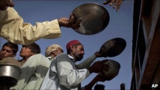 Pakistani men line up to receive a fresh meal at a camp for families displaced by floods run by the Pakistan Air Force in Sukkur, Sindh province