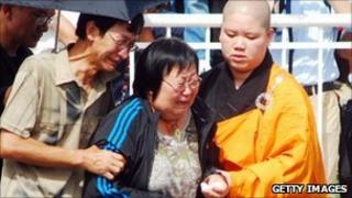 Buddhist monk comforts grieving family members in Manila