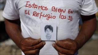 Alberto Segovia, outside the San Jose mine in Copiapo, Chile, shows a portrait of his brother Dario Segovia, 48, one of 33 miners trapped inside