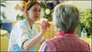 Nurse feeding elderly patient