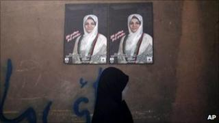 A woman walks past a campaign poster of Fauzia Galani in Herat, Afghanistan (26 August 2010)