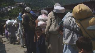 Local people queue to cross the bridge