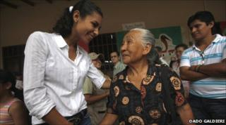 Jessica Anne Jordan Burton shakes the hand of an old lady while campaigning in Bolivia
