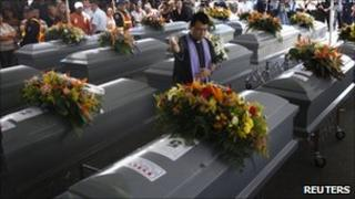 A priest blesses the coffins of 16 Hondurans killed in the massacre in Tamaulipas in August