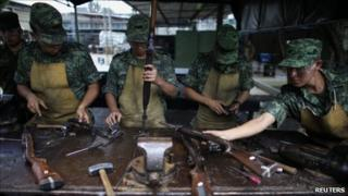 Mexican soldiers dismantle guns seized from alleged drug traffickers