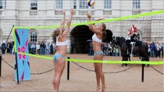 Lucy Boulton (left) and Denise Johns, members of the Team GB Beach Volleyball team, playing Beach Volleyball against a backdrop of the Household Cavalry Mounted Regiment Changing of the Guard, at Horse Guards Parade
