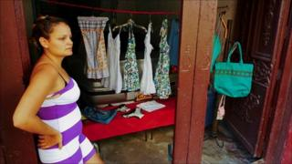 seamstress stands outside shop