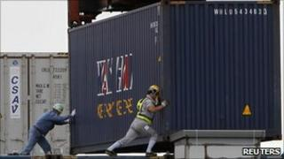 Workers load a container ship in the port of Tokyo