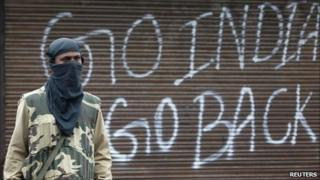 An Indian policeman stands guard near a closed shop during a curfew in Srinagar on Tuesday 14 September 2010