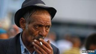 A deported Roma man smokes after arriving by air in Bucharest from Marseille, 14 September