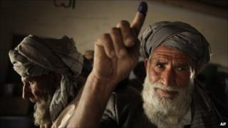 An elderly Pashtun man holds up his ink-stained finger as he votes in the parliamentary elections in Kabul