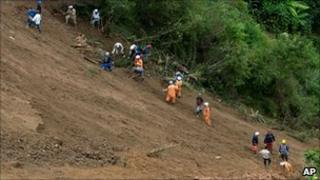 Rescuers search for victims of a landslide near Giraldo, Colombia