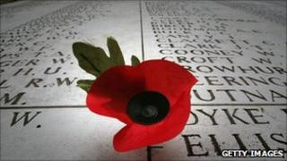 A remembrance poppy on a memorial displaying the names of some of the missing from WWI and WWII in Ypres, Belgium, on 5 November 2008