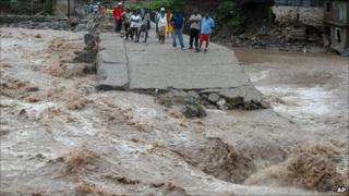 Residents stand on a destroyed bridge that linked the towns of Kintyre and Kingston in Jamaica