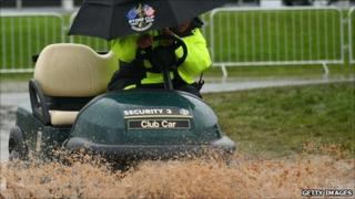A golf cart negotiates the rain and mud at the Celtic Manor Resort on Sunday