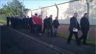 Workers walking along wire fence