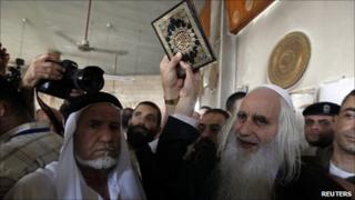 Rabbi Menachem Froman holds up a Koran at the fire-damaged mosque in Beit Fajjar (5 October 2010)