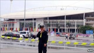 A military policeman stands outside the My Dinh stadium after the explosion (6 October 2010)