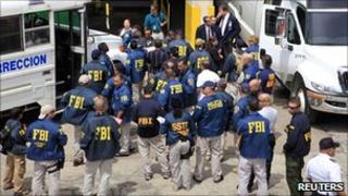 FBI agents wait to escort arrested police and prison officers