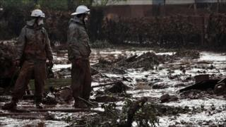 Hungarian firefighters, wearing protective gear, survey a yard flooded by toxic mud in the village of Kolontar, Hungary, Thursday, Oct. 7, 2010.