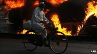 Cyclist passes burning Nato supply tanker