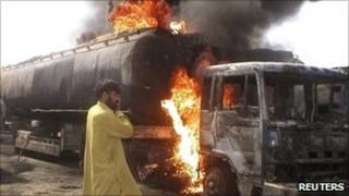 Truck driver watches as fuel tankers burn after they were set ablaze at Sibi, in the Balochistan area of Pakistan