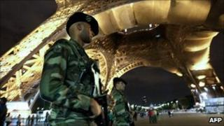 French soldiers patrol underneath the Eiffel Tower in Paris on 3 October 2010