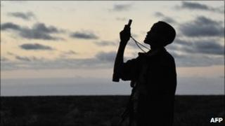 Somali gunman looks for a mobile phone signal (file photo)