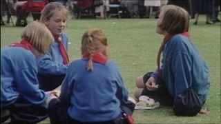girl guides sitting on grass