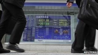 Businessmen walk past Nikkei electronic screen