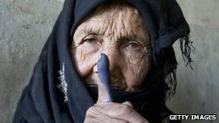 An elderly woman shows off her inked finger after casting her vote in Kabul
