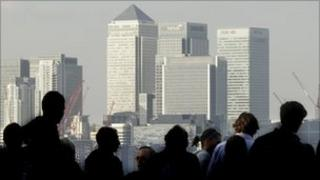 Workers silhouetted in front of the Canary Wharf skyline