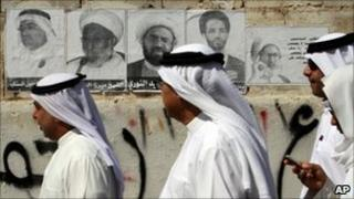 Bahraini men walk by a wall with posters of jailed Shia activists, 22 October