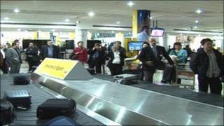 Passengers at Cairo airport luggage carousel