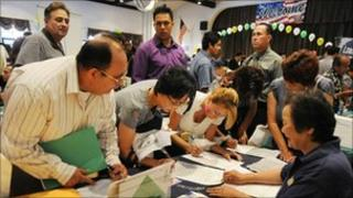 Unemployment Americans attend a job fair in California