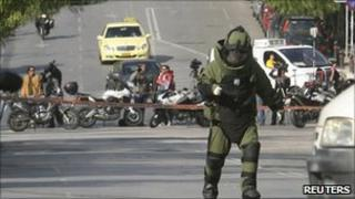 A police explosives expert arrives to detonate a suspicious package (1 Nov 2010)