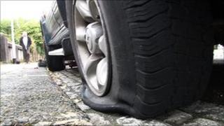 Slashed tyre on car