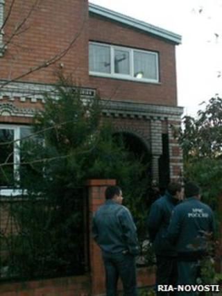 Emergency workers stand outside the house where the murders occurred