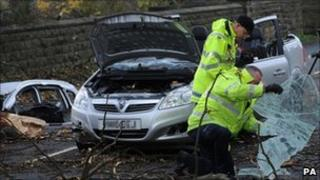 Investigators examine the scene where a woman died after a tree hit her car during stormy weather in West Yorkshire on Thursday 11 November