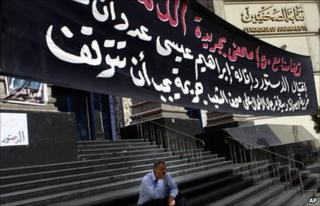An Egyptian journalist sits under a slogan supporting Ibrahim Issa outside the Syndicate of Journalists in Cairo (18 October 2010)