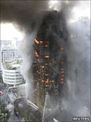 Firefighters try to extinguish a fire at a building in Shanghai, China, 15 November 2010