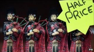 bagpipe figures with a half price sale sign