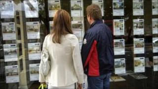 Two people looking in an estate agent's window