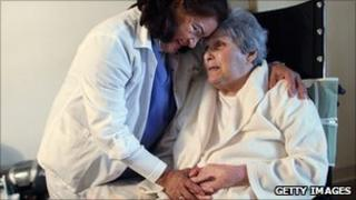 Home care worker comforting elderly woman in wheelchair