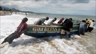 Fishermen pushing their boat out to sea in Sierra Leone