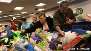 Shoppers search bins for toys at a Goodwill thrift store in Denver on Black Friday