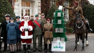 Trooper Kuziva Dapira of the Kings Troop Royal Horse Artillery, riding his horse Caprice, places a uk4u Thanks! gift box on a Christmas tree stand in St Johns Wood Barracks