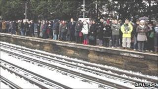 Commuters wait in the snow for a Tube train at Parsons Green station